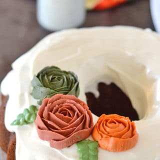 A close up of a pumpkin cake on a plate with frosting on top