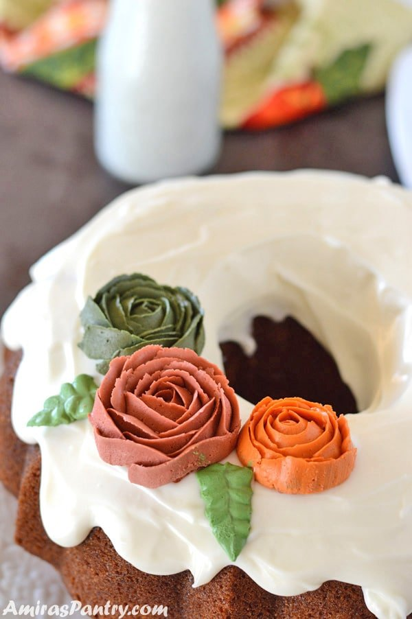 Moist pumpkin cake with cream cheese frosting topped with buttercream roses.
