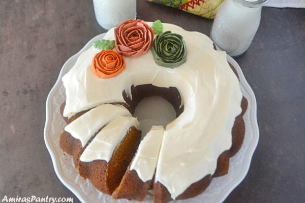 Moist pumpkin cake with cream cheese frosting on a white plate with milk cups behind