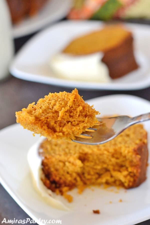 A fork holding a piece of moist pumpkin cake awith slices of the cak in plates on the background.