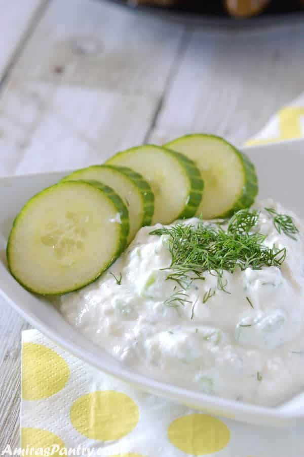 A white triangular shaped plate with tzatziki sauce and some cucumber rings on the side