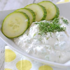 A close up for a plate with Tzatziki and cut cocumbers