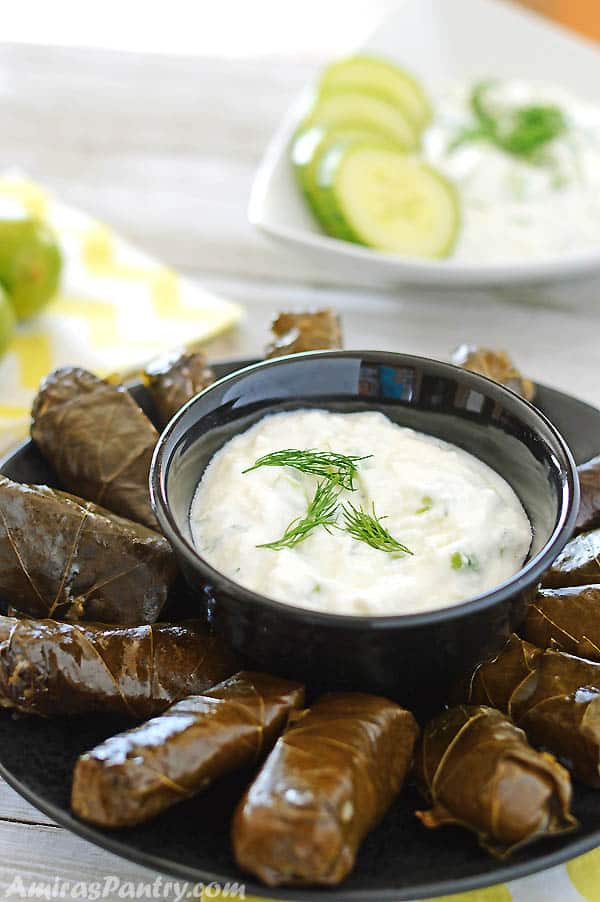 A small black bow with tzatziki sauce surrounded by stuffed grap leaves.