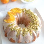 An orange cake on a plate with orange on top