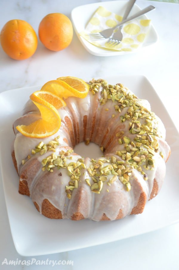 Golden saffron orange bundt cake on a white serving plate.