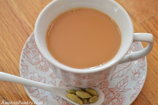 A cup of spicy Middle eastern tea with a spoon of cardamom to the side.