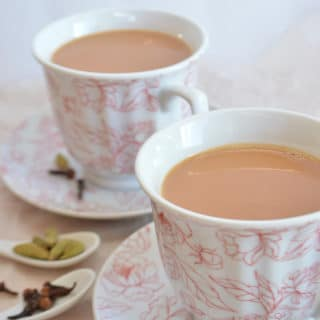 Two cups of spiced tea on plates