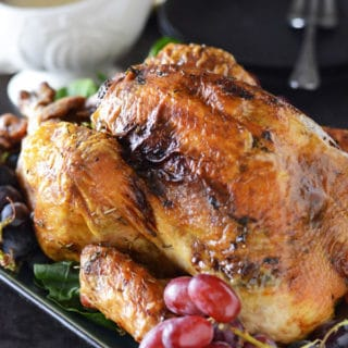 A close up of a plate with roasted turkey on top