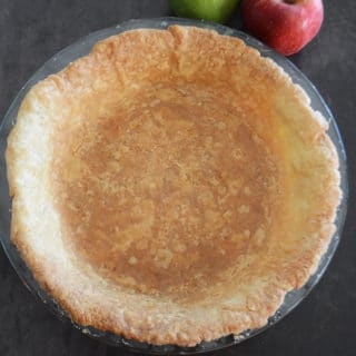 An apple sitting on top of a table, and a close up of food, with Pie crust