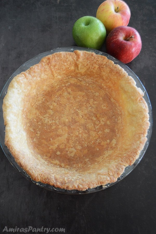 A blind baked pie crust on a glass bakeware with three apples in the back.