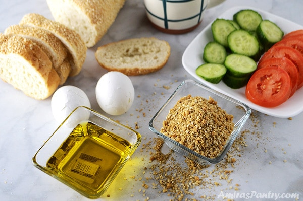 Breakfast table of a small bowl of dukkah spice with another one of oil along with crusty bread, hard boiled eggs and a plate with slices of cucumber and toamtos.