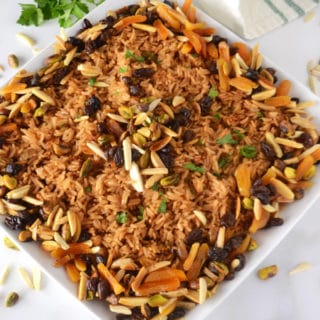 A plate of food on a table, with Pilaf rice, raisins and nuts