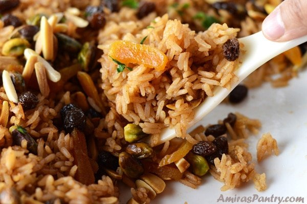 A close up on a plate of food, with Pilaf Rice and nuts