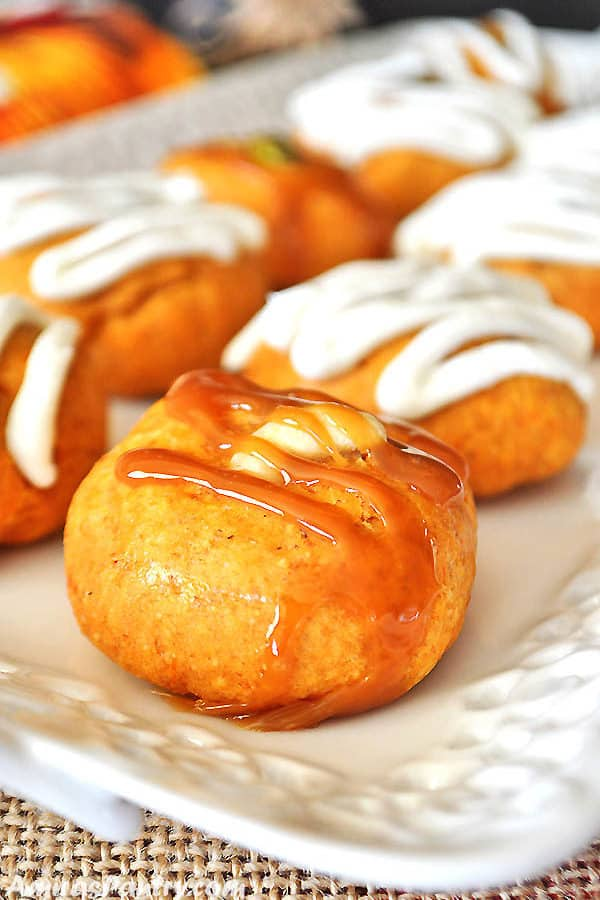 A white serving plate with sweet potato cookies topped with caramel sauce.