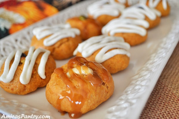 A white serving plate with sweet potato cookies topped with caramel sauce ans white sauce.