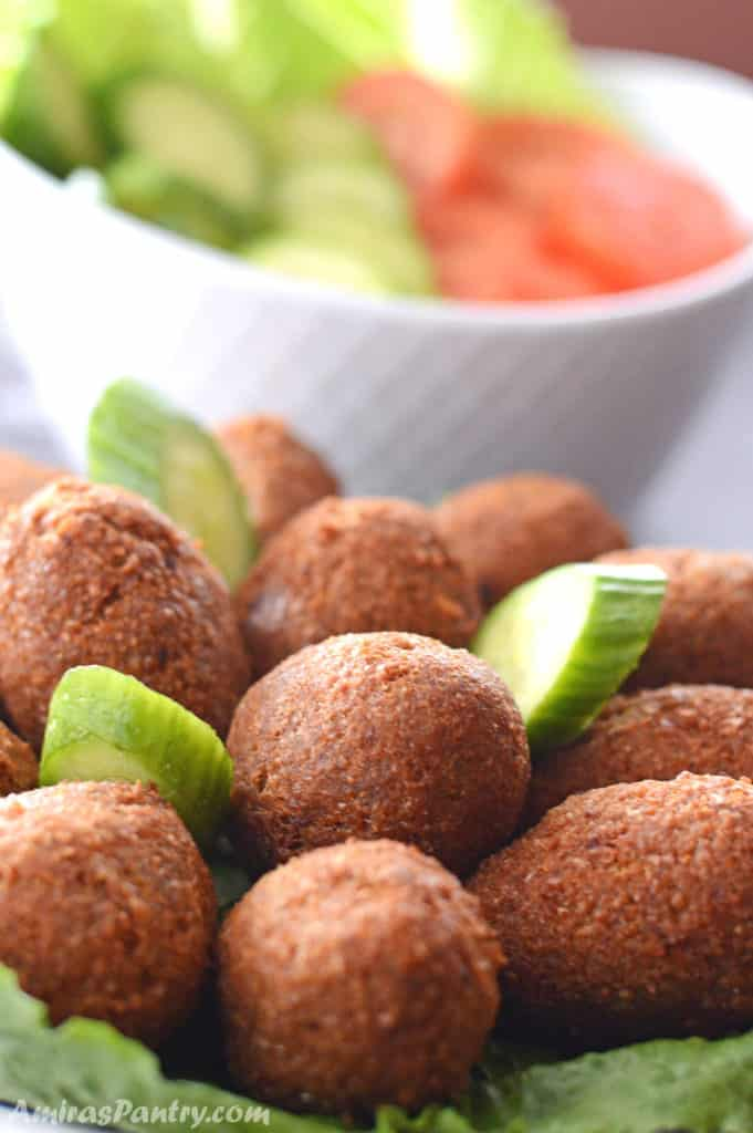 A big serving plate with kibbeh on a table with another plate of cucumber and tomato slices.