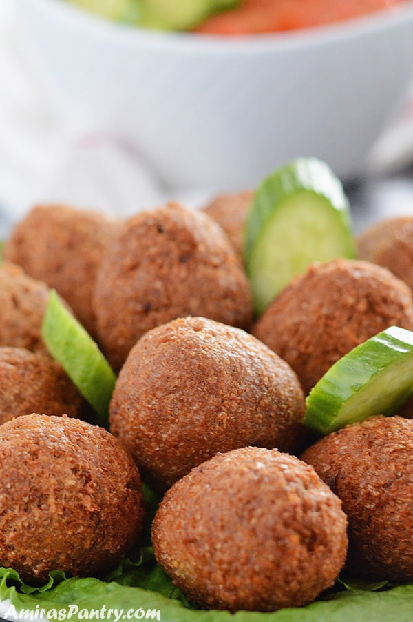 A pile of kibbeh on a plate with cucumber slices.