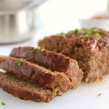 A close up look at a sliced meatloaf placed on a white plate.