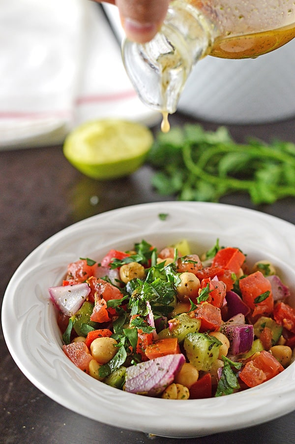 A hand pouring lime and olive oil dressing over a small white bowl of Mediterranean chickpea salad.