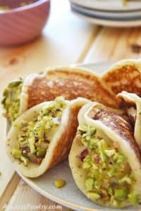 A white plate with some stuffed qatayef dipped in pistachios with a small bowl filled with crushed pistachios on the back.