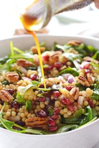 A bottle pouring dressing over mediterranean couscous salad