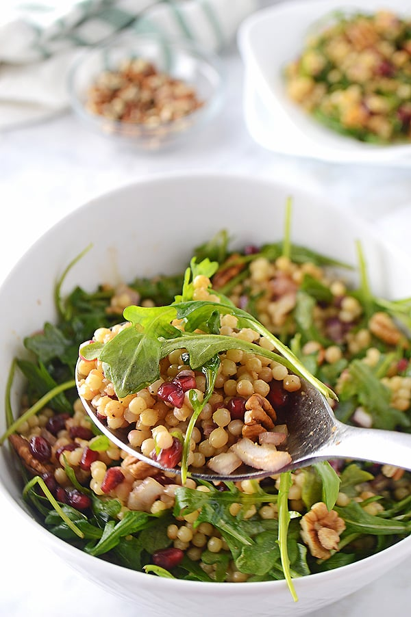 A spoon scooping some of the Mediterranean couscous salad with the whole bowl in the back.