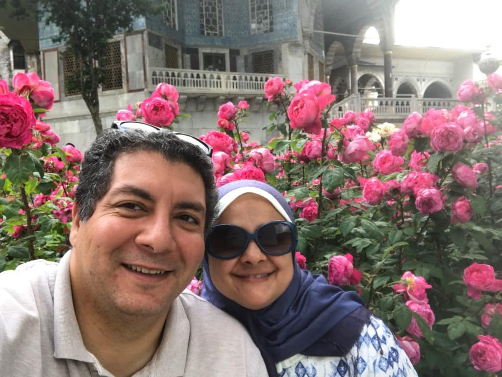 Amira and her husband standing in front of a building