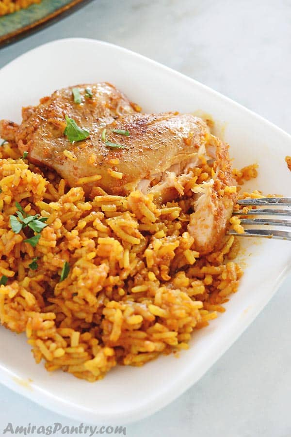 A plate of food with rice pilaf, chicken and vegetables