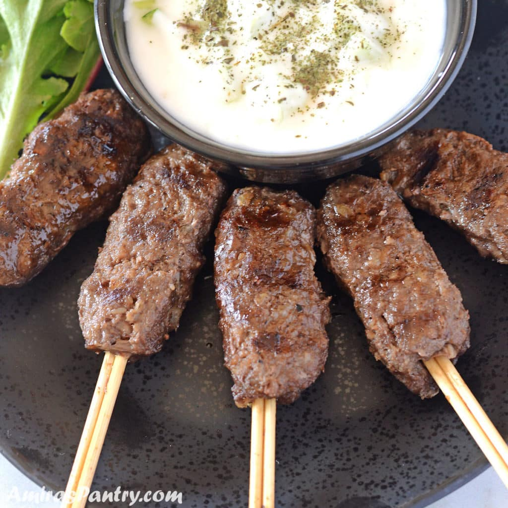 Kofta skewers on a black plate with a bowl of tzatziki sauce