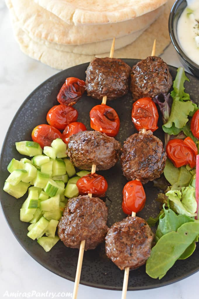 Kofta skewers with tomato on a black plate we diced cucumber and pita bread in the back