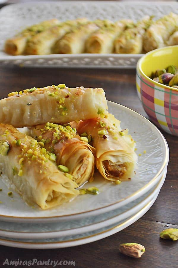 Baklava rolls placed on a stack of white plates