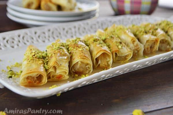 Baklava rolls on a white plate and sprinkled with crushed pistachios.