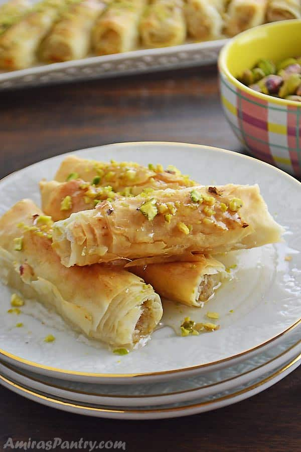 Phyllo rolls placed on a stack of white plates and sprinkled with pistachios.