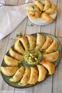 Beef empanadas on a big green platter with a bowl of guacamole in the middle