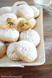 A white plate with kahk cookies dusted with powdered sugar with one open at the top.