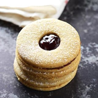 A stack of linzer cookies filled with jam with a white kitchen cloth in the back.