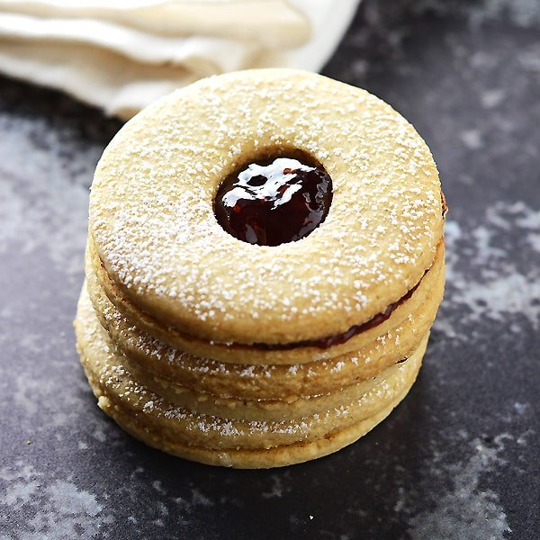 A stack of Linzer cookies on a dark surface.