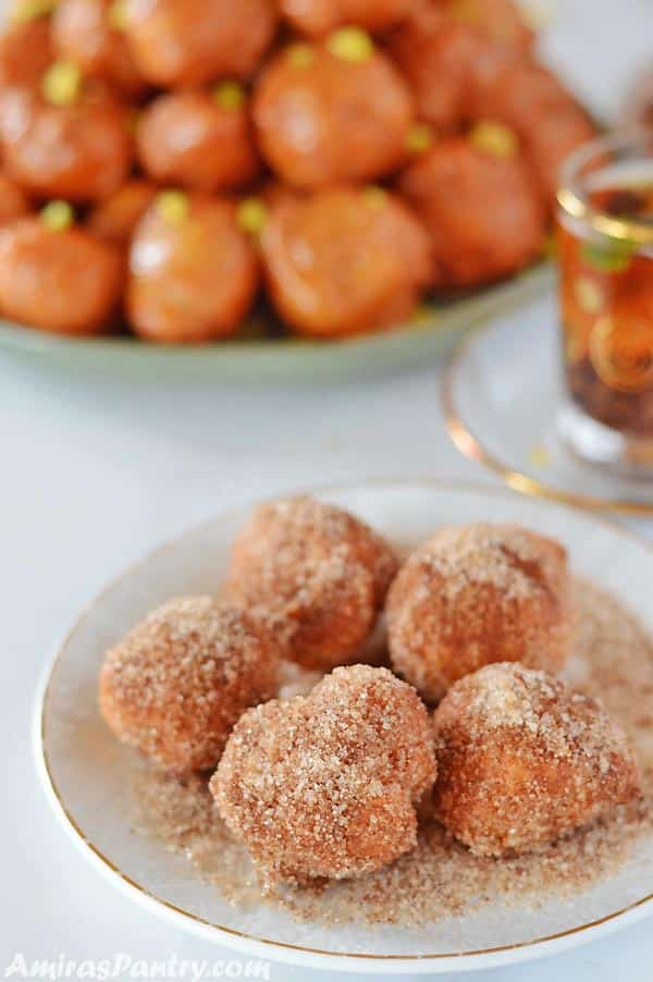 Some loukoumades balls covered in cinnamon sugar and placed in a small dessert plate with a cup of tea on the back.