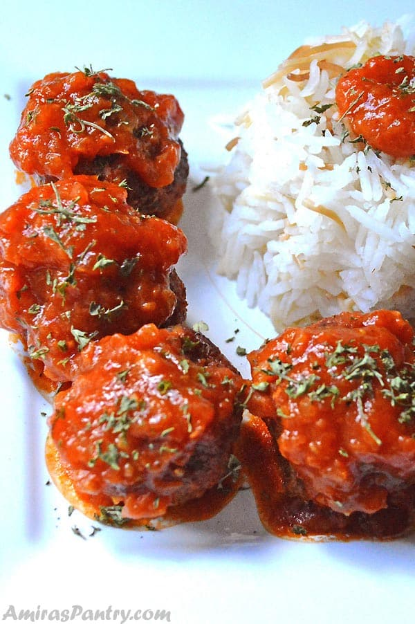 Rice meatballs on a white plate topped with tomato sauce.