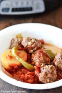 meatballs with potato and green bell pepper in a white plate.