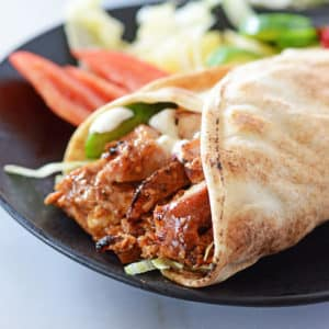 A close up of Chicken shawarma wrapped in pita bread