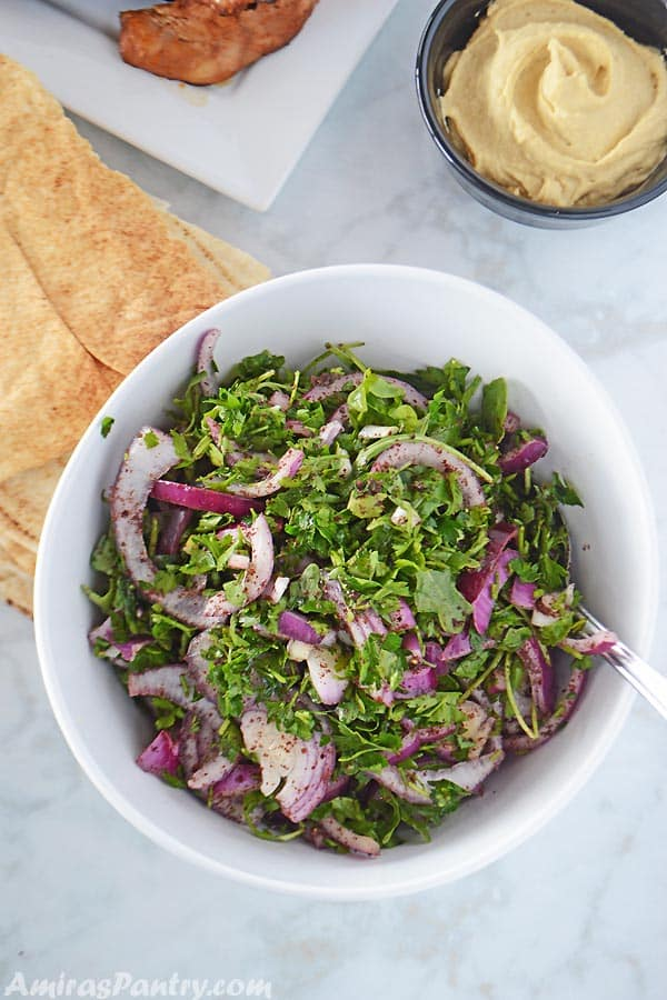 A white serving bowl with arugula salad with some pita bread on the side