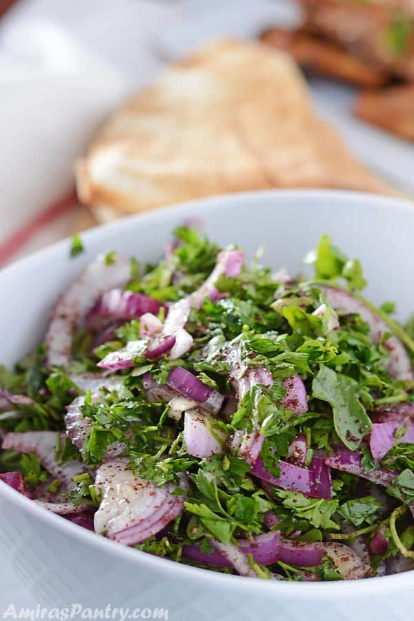 A white serving bowl with arugula onion salad with some pita and grilled chicken on the side