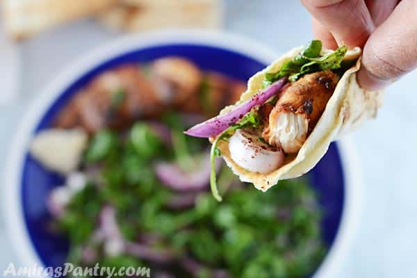 A hand holding a piece of pita bread with grilled chicken and arugula salad.