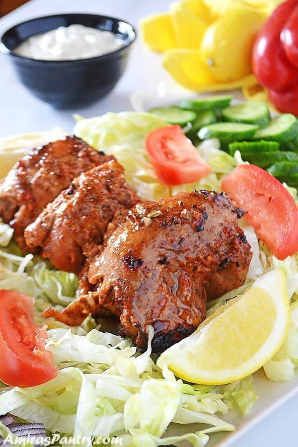 Chicken Shawarma on a bed of lettuce with cucumber, tomato and lemon wedges on the side