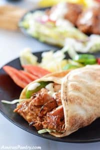 Chicken shawarma wrap on a black plate with some pickles and lettuce on the side.