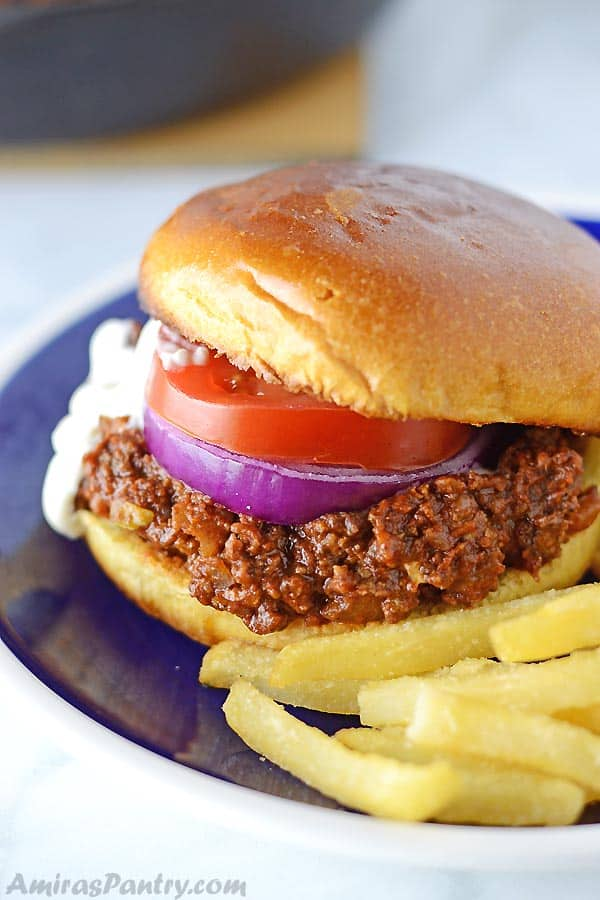 A sloppy joes sandwich placed on a blue plate with fries on the side.