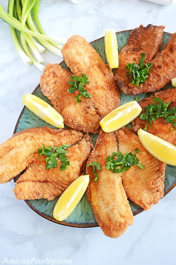 Fried tilapia fillets on a green oval serving platter with lemon wedges.