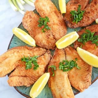 A plate of food, with fried Tilapia and lemons