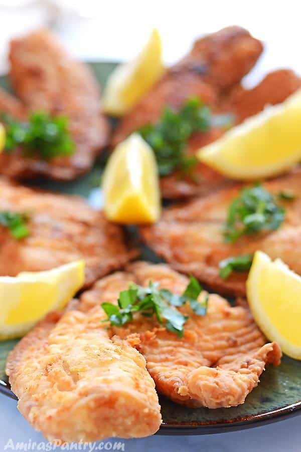 Tilapia fillets on a green platter decorated with lemon wedges and chopped parsley.